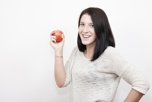 Best fruits for acne. A girl eating an apple
